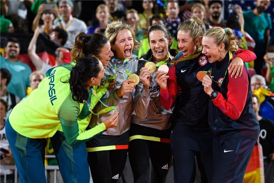 Olympic champions Laura Ludwig and Kira Walkenhorst (center) with Agatha/Barbara (left, silver) and Kerri Walsh and April Ross (right, bronze) celebrate in Rio. Photo: FIVB